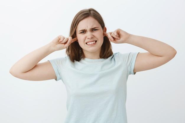 dziewczyna zamyka uszy czujac sie niezadowolona gdy ludzie walcza w jej poblizu intensywnie niezadowolona mloda kobieta zaciskajaca zeby z powodu dyskomfortu przejmuj