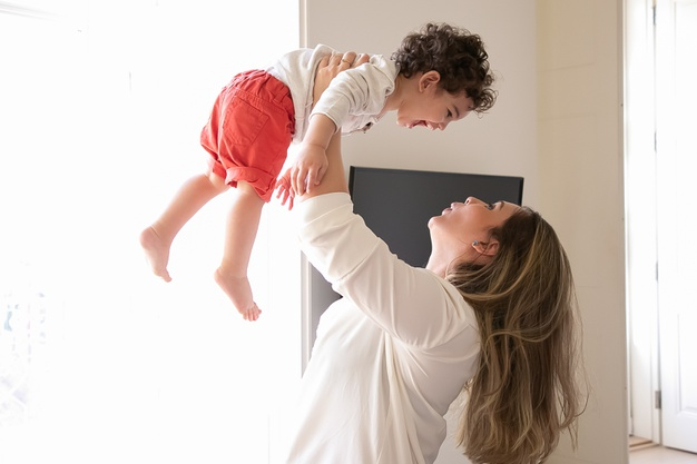 happy mom holding excited baby arms lifting child air side view parenthood childhood concept 74855 12880