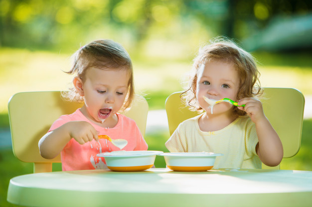 two little 2 years old girls sitting table eating together against green lawn 155003 13550