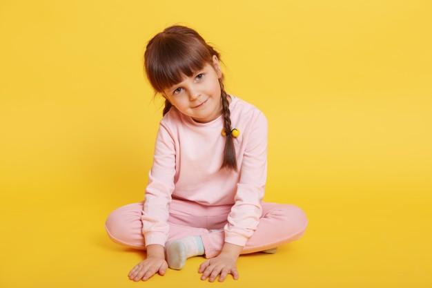 wesola atrakcyjna dziewczynka siedzi na podlodze ze skrzyzowanymi nogami dotykajac podlogi dlonmi patrzac na kamery pozowanie na bialym tle na zoltym tle ubiera bladorozowy stroj 176532 13691